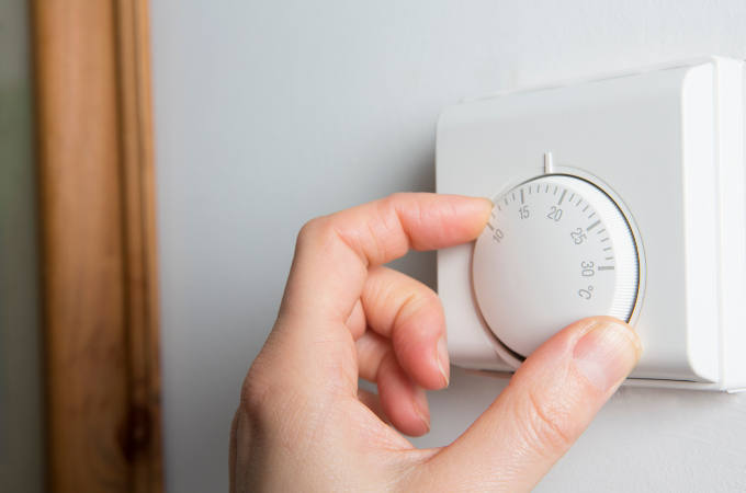 Close up of someone adjusting the central heating thermostat