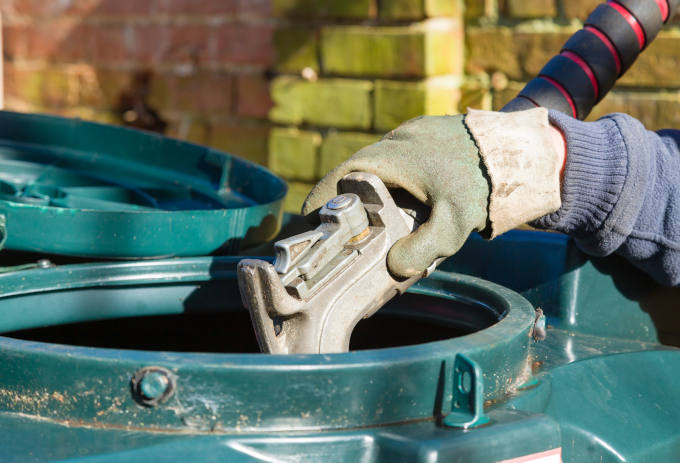 Closeup of man filling a bunded oil tank with domestic heating oil